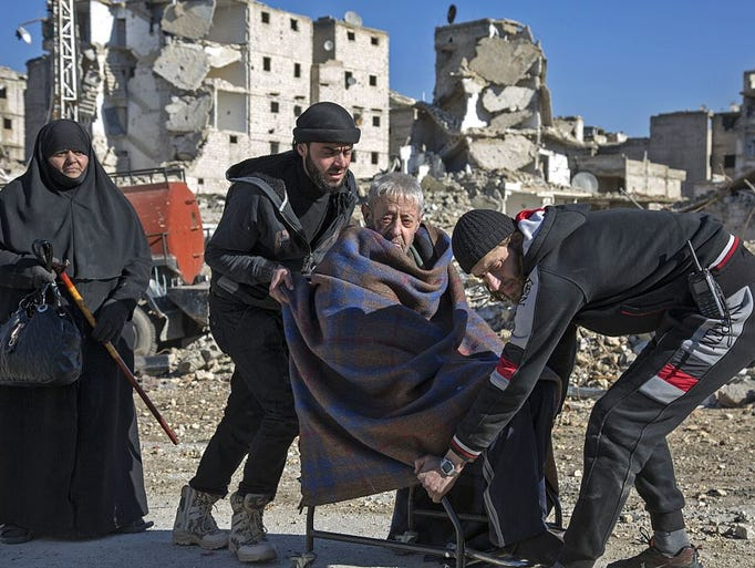 An elderly Syrian man is carried during an evacuation