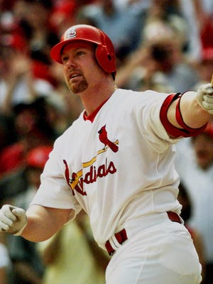 Mark McGwire watches his record-setting 70th home run against the Montreal Expos' Carl Pavano on Sept. 27, 1998.