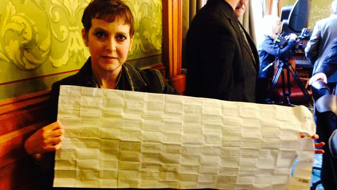 Lung-cancer patient Lori Tassin of Des Moines holds up an insert listing all the possible side-effects of a chemotherapy drug she takes. Tassin was appearing at an Iowa Senate hearing in February. She told senators she didn't understand why they wouldn't let her try marijuana, which has fewer side-effects.