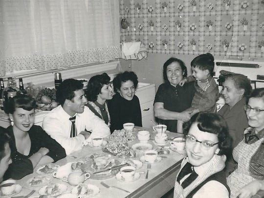 Kristin D'Agostino's ancestors enjoy a meal at the table in Hawthorne, N.J. circa 1954. Her father Joseph, to whom this poem is dedicated, is the little boy sitting happily in his grandmother's lap.