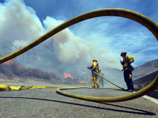 Firefighters battle the Bluecut Fire along Swarthout
