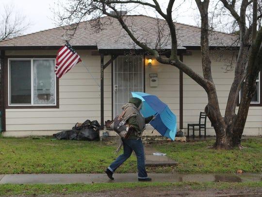 A woman walks through stormy weather Tuesday through downtown Redding.