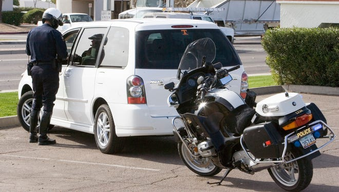 photo by Michael Ging /Arizona Republic,(1/24/06) 131120 gl-intersection03, Here near 92 ave and Bell rd. Peoria Traffic Enforcement Motor Officer, Norm Bacon (cq) writes a speeding ticket to a driver for 56 mph in a 40 mph zone. The person was speeding west on Bell rd. near 92nd ave.