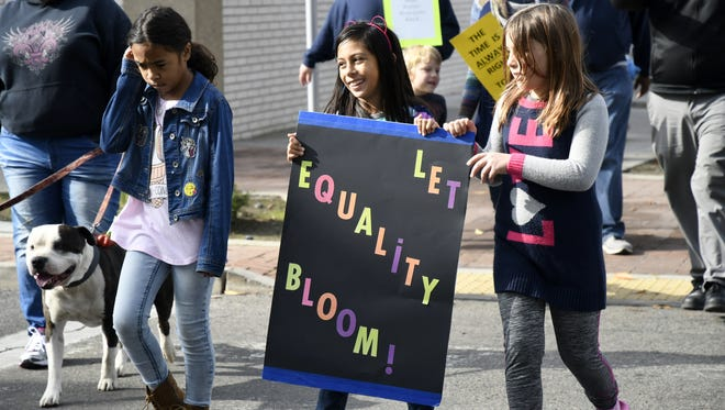 Keilani Gates-Wai, 9, Diana Padilla, 9, and Zoe Bigler, 9, march down Main Street during the Boys and Girls Club of the Sequoias annual MLK Jr. Day march on Monday.