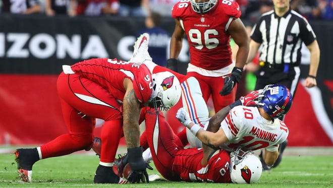Arizona Cardinals defensive tackle Robert Nkemdiche (90) recovers a fumble after linebacker Deone Bucannon (20) forced a fumble by New York Giants quarterback Eli Manning (10) in the fourth quarter at University of Phoenix Stadium.
