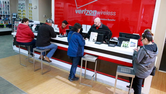 Jeremy Goodwin, center, manager of The Cellular Connection, helps a customer on Friday at the store at 4323 E. Main St. in Farmington.