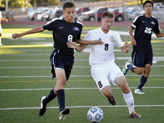 Piedra Vista's Angel Flores, left, and Farmington's Andrew Moss chase down the ball during a 2014 game at Hutchison Stadium in Farmington.