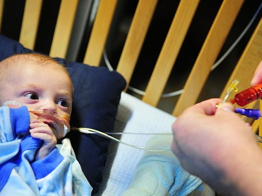 Houston Schwartz, then 5 months old, watches from his crib as father Matt administers Tylenol via a tube in the basement of Matt's mother's Springettsbury Township in April.