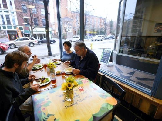 """From left, Cameron Naylor of Felton, Greg Briggs of Springettsbury Township, Audrey Bowen of Springettsbury Township, and Dave Naylor of Felton have dinner at the front table with a view of the city during the community sneak peak at Healthy World Cafe on the first block of South George Street in York Friday, April 3, 2015.  Healthy World Cafe is a """"pay how you can"""" restaurant. Customers may pay a full suggested price, volunteer their time for a meal, or pay it forward - adding an extra amount to the suggested price to help pay for volunteer meals. Food at the cafe is locally sourced and made from scratch."""
