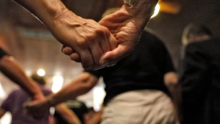 People at a prayer vigil at the Joy Metropolitan Church hold hands for the shooting victims at the Pulse nightclub in Orlando.