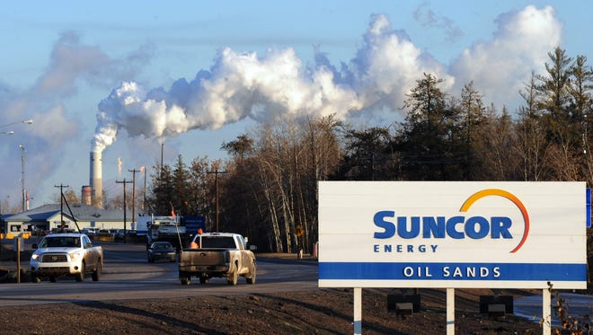 Workers leave the Suncor oil sands extraction facility near the town of Fort McMurray in Alberta Province, Canada.