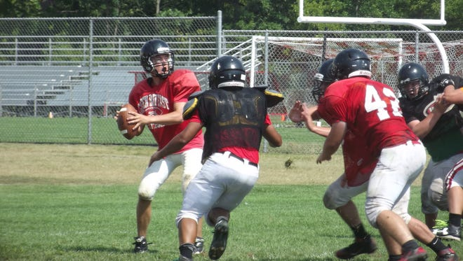 Green Bay East sophomore quarterback Koda Kinjerski looks to avoid the rush before releasing a pass at practice Tuesday.