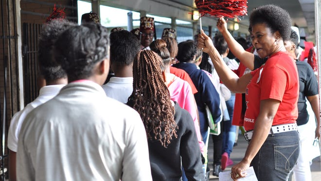 Stephanie Hunter, an eight-grade teacher at Arthur F. Smith Middle Magnet, cheers on students Friday morning after a pep rally to motivate the school for LEAP testing, which begins on Monday.