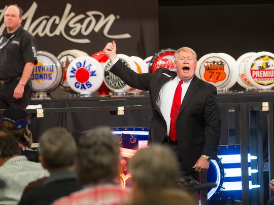 Auctioneer Tom Johnson takes bids on automobilia at