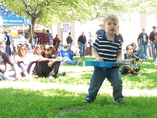Robby Remuzzi, 2, of Burlington, strums a plastic guitar Saturday while listening and dancing to The Wee Trio at the Burlington Discover Jazz Festival in City Hall Park.