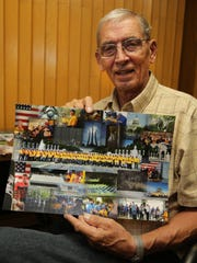 Air Force veteran Wayne Schoepke of Wausau holds up a photo montage from the Never Forgotten Honor Flight he went on in May.