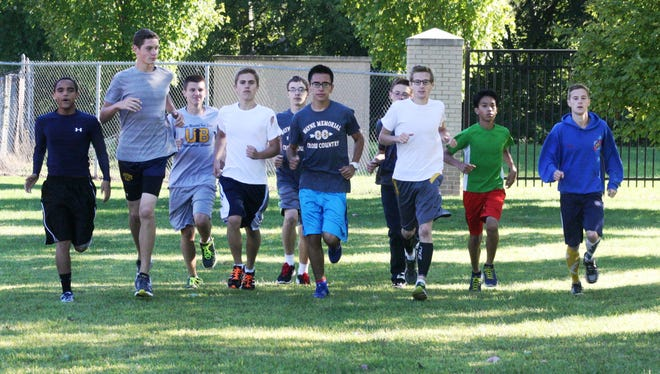 Members of the Wayne Memorial cross country team are pictured stretching out following a recent practice.