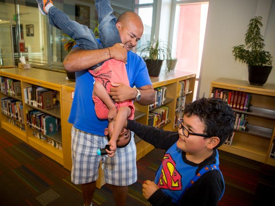 Steven Cano holds his son, 6-year-old Emilio Cano in the Centennial High School library while his other son, 9-year-old Angelo Cano, looks on.