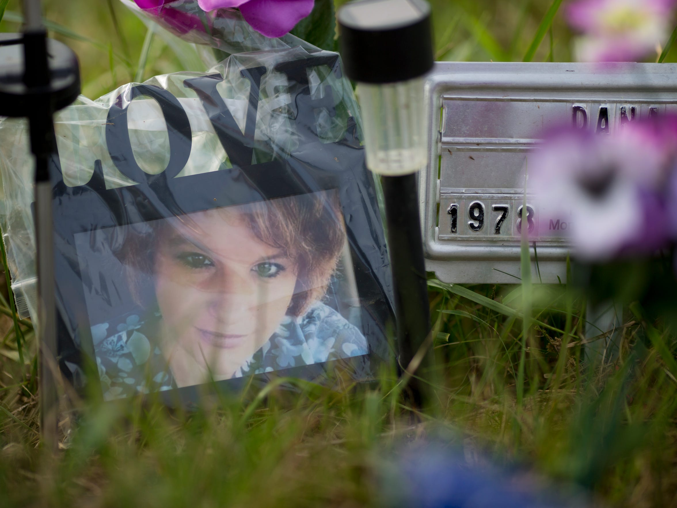 Aug. 24, 2016: A picture of Dana Rhoden sits atop her grave site at Scioto Burial Park, where she was laid to rest beside her husband, daughter, and two sons.