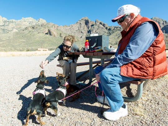 "Bill Beschle and his wife Sue enjoy lunch with their three dogs on Tuesday, January 31, 2017, at a picnic table in the entrance of the Organ Mountain-Desert Peaks National Monument. Bill Beschle, who works at the Scenic View rest area,  said since the area was designated as a national monument ""Many travelers come by and ask where the monument is and how to get to it."""