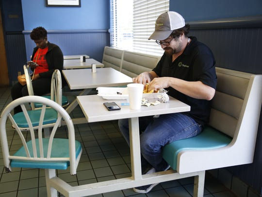 Trulieve employee Jeremy Sullivan eats lunch at AJ's Chicken & Things in Quincy Wednesday, April 25, 2018. He says it's the third time he's eaten there that week.