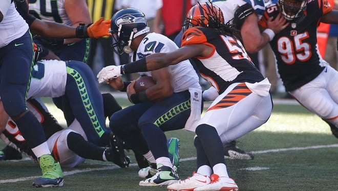 Seattle Seahawks quarterback Russell Wilson (3) is sacked by Cincinnati Bengals outside linebacker Emmanuel Lamur (59) in overtime of an NFL football game, Sunday, Oct. 11, 2015, in Cincinnati. The Bengals won 27-24.
