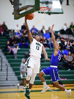 Going in for a layup Friday night is Novi's Jiovanni Miles (13). Trying to defend is Salem's Cameron Grace (23).