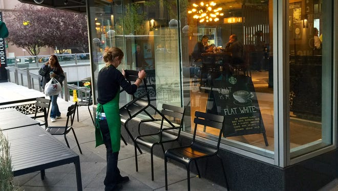 A worker at the Starbucks coffee shop on Denver's 16th Street pedestrian mall stacks chairs prior to closing the doors early 8 p.m. due to computer problems.