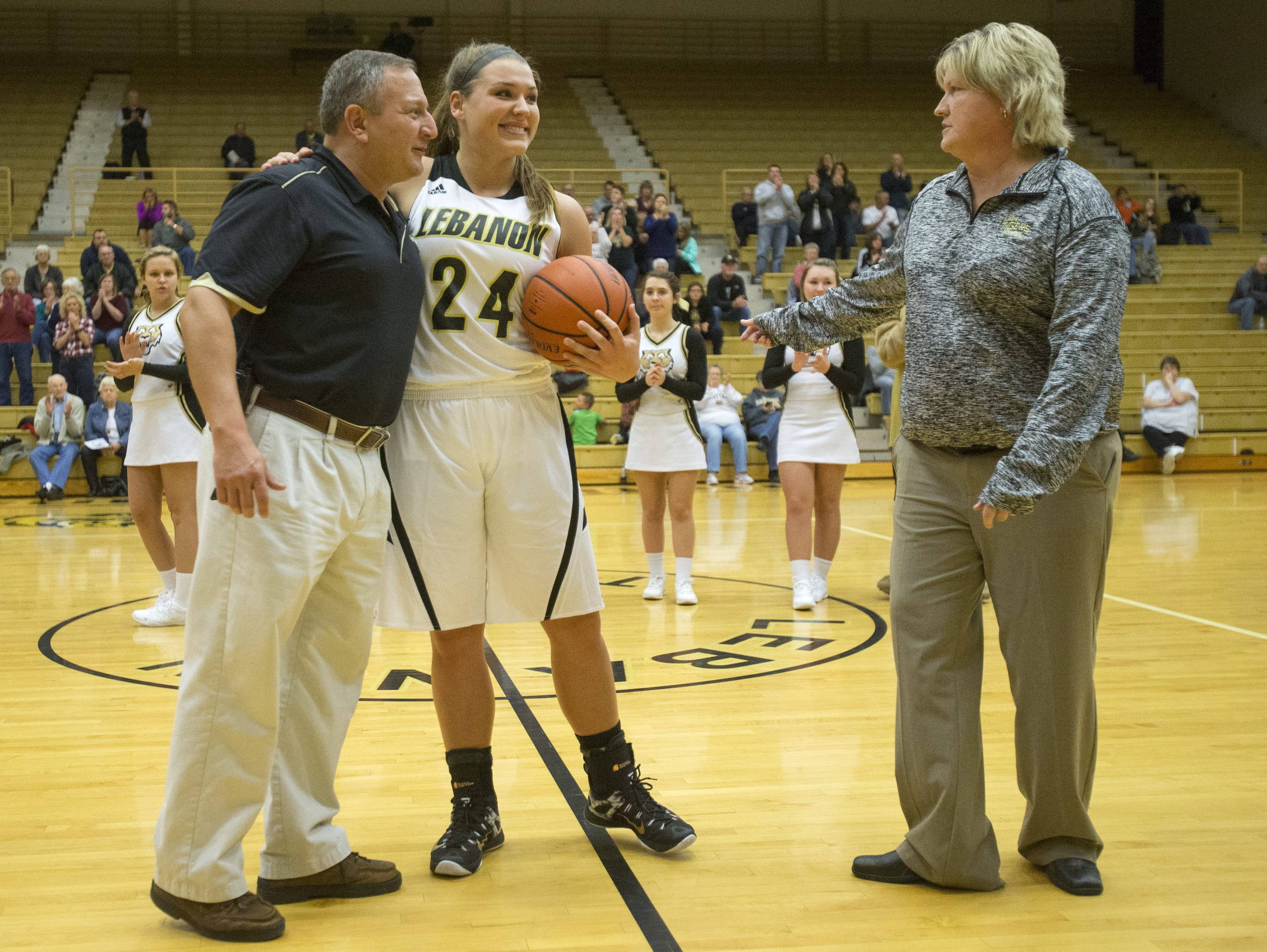 Kristen Spolyar is recognized by Lebanon AD Phil Levine (left) and coach Beth DeVinney after scoring her 2,000th point.