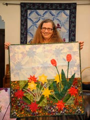 "Suzanne Kistler, 55, of Visalia holds up her quilt ""Sentries in the Garden."" She is the chairwoman for the Best of the Valley Quilt Show April 10-12 at the McDermont Field House in Lindsay. She was a self-taught quilter until she joined the Valley Oak Quilt Guild in Tulare."