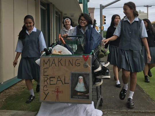 The Walking Nuns, a club at the Academy of Our Lady of Guam, push a cart full of necessities -- food, clothing, shoes and hygienic products -- for those in need Hagåtña.