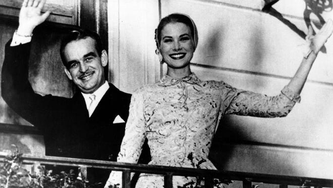 Prince Rainier III and Princess Grace Kelly wave from the Monaco palace terrace after their civil wedding ceremony.