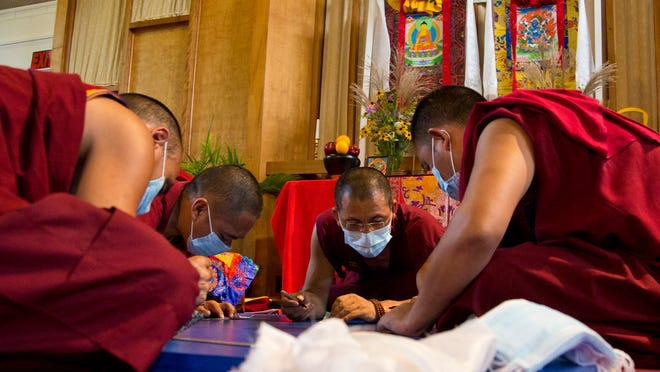 Tibetan Buddhist monks from Drepung Gomang Monastery work on creating a sacred Green Tara sand mandala Wednesday at Unitarian Universalist Church in West Lafayette. A deconstruction ceremony will be held Sept. 10 with a procession to the Wabash River following.