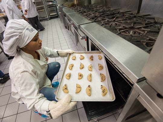 Raevyn Moore, a sophomore at Middletown High School places a tray of unbaked cookies, donated by Bob Evans, into an oven.  The cookies will be sent to troops stationed overseas with a partnership with the American Legion Unit 25 in Middletown.