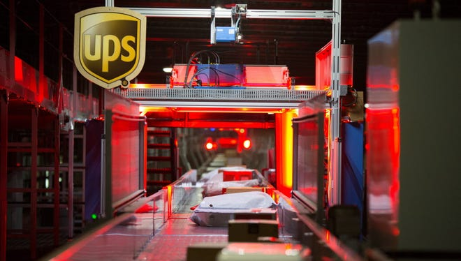 Packages move on a high-speed conveyor belt as they make their way to UPS's infrared technology system.