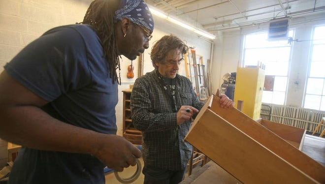 Jonathan Jason, program director at Pivot in Dobbs Ferry, works with Charles Reaves of the Bronx as they restore old drawers Dec. 11, 2014. Pivot is a social enterprise that helps people with criminal backgrounds learn how to make furniture and art. The company restores old furniture. It also creates original furniture, as well as works of art, often from donated and unusable musical instruments. Reaves, originally from Mamaroneck, is a former drug addict who spent time in prison. He has worked at Pivot for two years.
