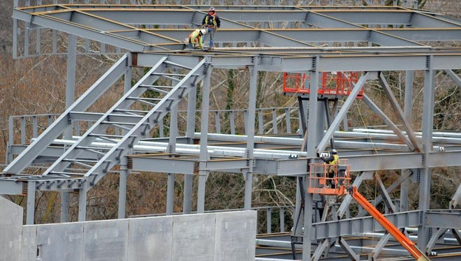 Workers frame the upper steel superstructure of the New Belgium Brewing Company brewery Tuesday on the west side of the French Broad River in Asheville.