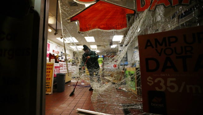 Sonny Dayan, a owner of cell phone and electronic  store cleans up after protesters when on looting and burned business in Ferguson after the grand jury decided not to indict Officer Darren Wilson, in the shooting of Michael Brown.