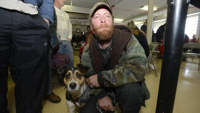 A man holds his dog at the Haywood Street Congregation Christmas service in the sanctuary at the Central United Methodist Church in 2013.