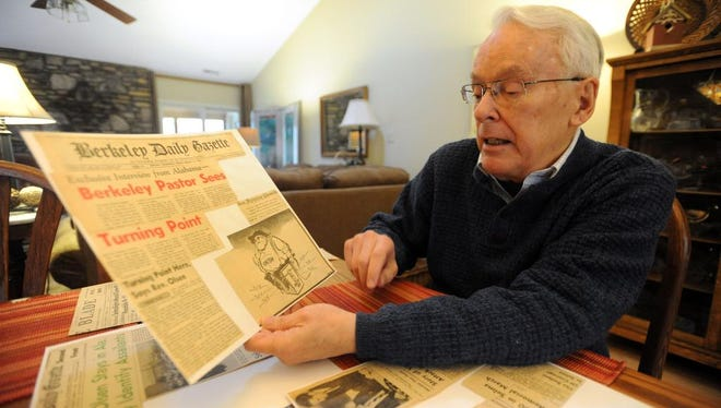 The Rev. Clark Olsen, a figure in the Selma, Alabama, protests looks over old newspaper clippings of the voter rights protests in 1965 at his home in East Asheville in this 2015 photo. Olsen witnessed the murder of the Rev. James Reeb, a turning point in the movement.