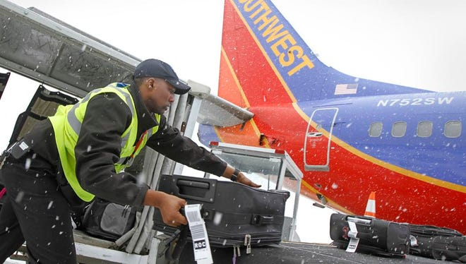 Kyran Ashford unloads luggage from a Southwestern flight at the Greater Rochester International Airport in January 2015.