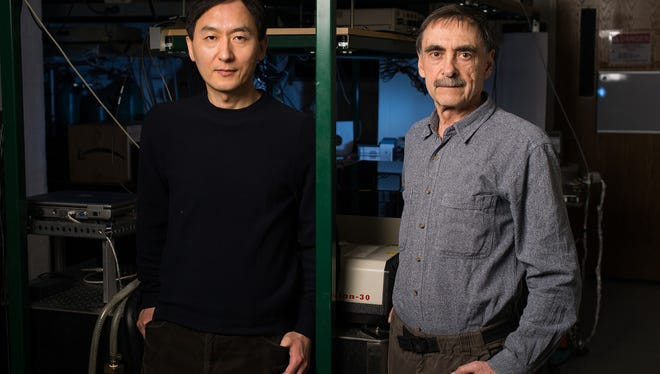 University of Rochester Institute of Optics professor Chunlei Guo, left, and senior scientist Anatoliy Vorobyev, photographed in their lab Feb. 12, 2014, have developed a technique that uses lasers to render metal water-repellent.