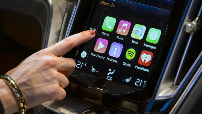 A visitor presses the new Apple's CarPlay touch-screen commands inside the Volvo Estate concept car displayed at the Swedish carmaker during the press day of the Geneva Motor Show in Geneva on March 4, 2014.
