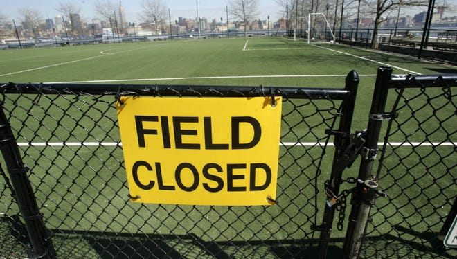 The locked gate of an artificial turf soccer field at Frank Sinatra Park in Hoboken, N.J., closed in 2008 after the New Jersey Health Department raised concerns about lead.