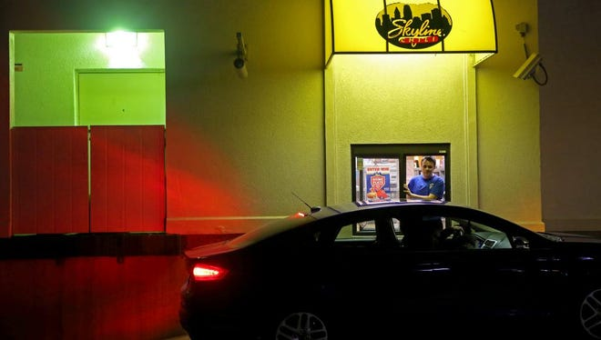 Ashton Dotson works the drive-thru window at Skyline in Delhi on Sunday, March 15, 2015. He likes to entertain customers and tell them jokes, while they are waiting for their food.
