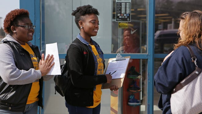 Esther Richards, left, 18, and Sabreen Jolly, 18, both students at Clark Atlanta University, talk with Sue Kern after learning that she is already a registered  in Ferguson, Mo.,  on Sunday, March 8, 2015.  Dozens of college students are forgoing traditional spring break plans at a beach or another easygoing destination and have instead arrived in Ferguson to encourage residents to vote in next month's election.