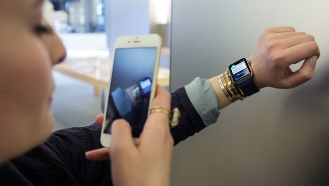 A French customer at an Apple store uses her smartphone to photograph her new Apple Watch, a visual sign of tech's increasing ubiquity.