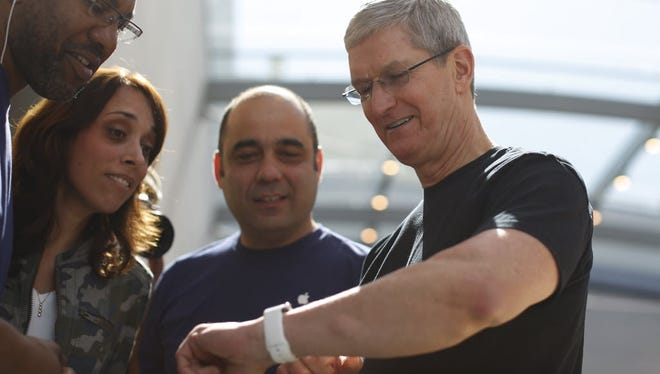 Apple CEO Tim Cook displays his personal Apple Watch to customers at an Apple Store on April 10, 2015, in Palo Alto, Calif.