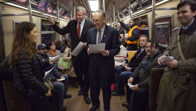 A woman accepts a flier from Sen. Charles Schumer, D-N.Y., center, as he and New York City Mayor Bill de Blasio ride the subway together in New York on April 9, 2015. During the ride, Schumer and de Blasio urged Congress to replenish the federal Highway Trust Fund, which is set to run out of money on May 31.