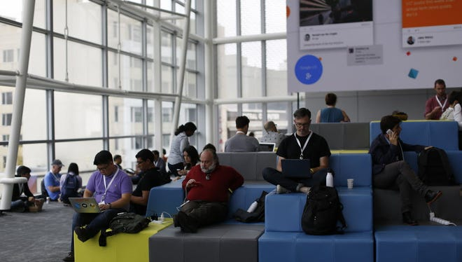 Attendees work on their computer and mobile devices during the Google I/O Developers Conference at Moscone Center on June 25, 2014 in San Francisco.